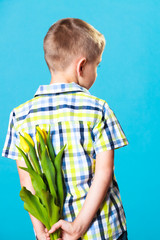 Boy hiding bouquet of flowers behind itself