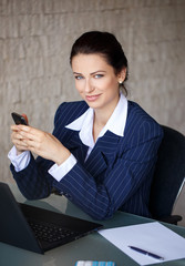 Confident businesswoman messaging in office