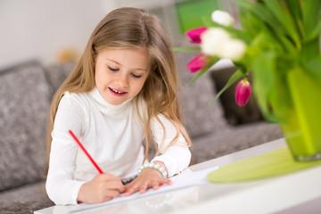 Happy little girl writing