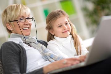 modern grandmother teaching grandchild how to use laptop