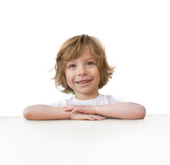 Adorable little boy on table edge isolated over white background
