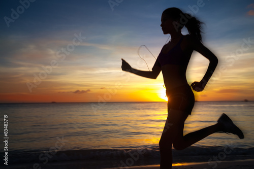 Silhouette of a woman running against the evening sky - in motio
