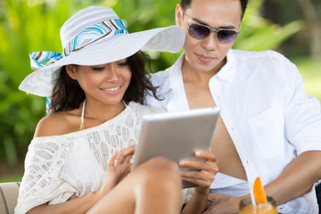 Young couple with tablet pc at tropical resort