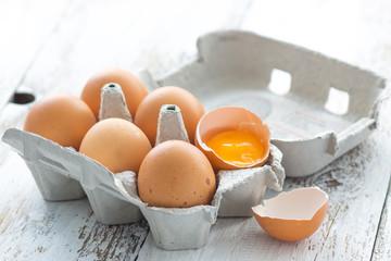 Cardboard box with eggs on wood