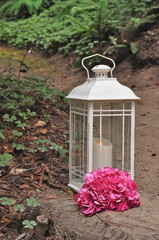 Outdoor lantern with burning candle and pink hydrangea flowers