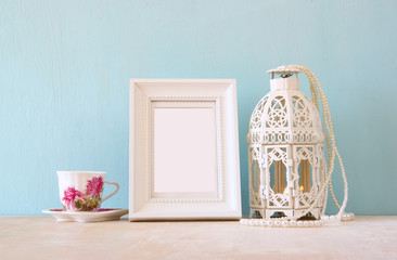 vintage classical white frame on wooden table with lantern