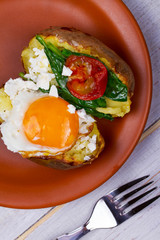 Baked potato with fried egg, feta, spinach and tomato cherry