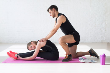 Girl doind exercise for flexible back and legs male trainer