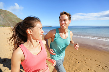 Young couple talking running on beach jogging