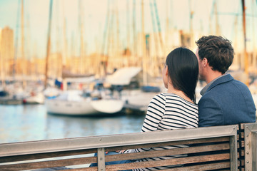 Lovers couple dating on bench in harbour Barcelona