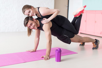 man doing push ups with woman laying on back at gym or home