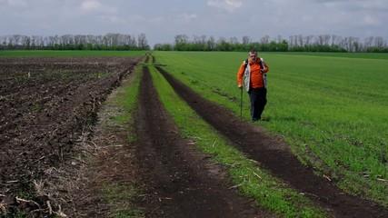 Senior man with walking stick walking on dirty road