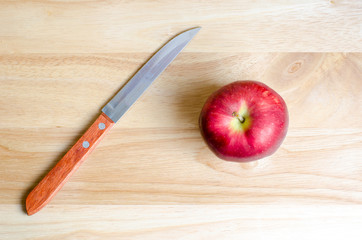 Red apple and knife on wooden table