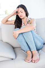 Pretty brunette with headache on couch