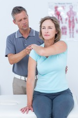 Woman stretching her arm with her doctor