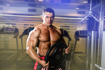 Handsome muscular man in the gym