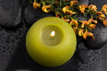 flowers and candle on black stones