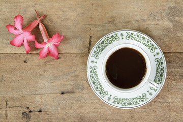 Coffee with plumeria flower on wooden plank background