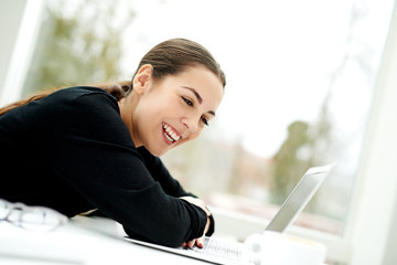 Young woman laughing as she reads her laptop