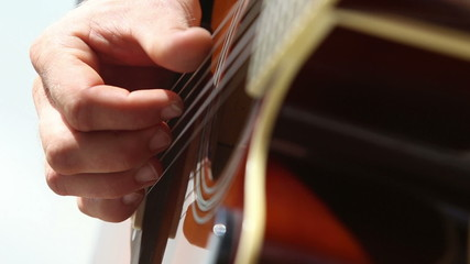 european man plays guitar with closeup focus on fingers