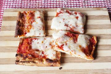 Tranci di pizza margherita su tagliere di legno