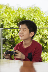 kid life, an Asian boy activity playing game with joystick
