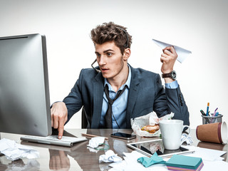 Office worker with paper plane in his hand typing on a computer