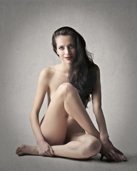 Naked woman sitting on the ground