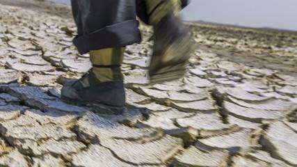 Feet Of Scientist Walking On Cracked Desert Earth