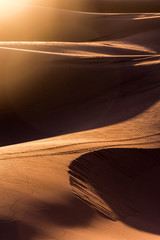 Sand dunes in the desert. Graphic lines and sun flare.