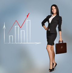 Young girl holding briefcase standing next to growth charts