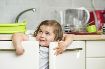 Beautiful little girl playing in the kitchen