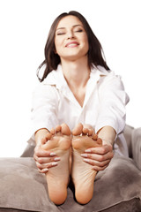 happy young woman massaging her feet