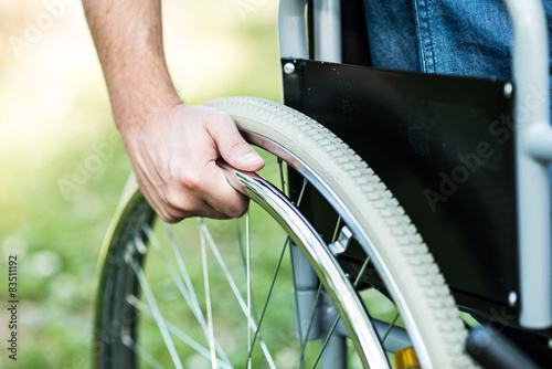 Poster Hand on the wheel of a wheelchair