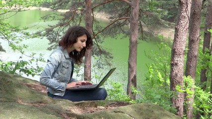 young woman with her laptop near a green lake