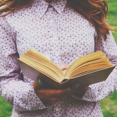 Young woman holding open book in her hands