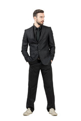 Bearded young businessman in sneakers looking awayy