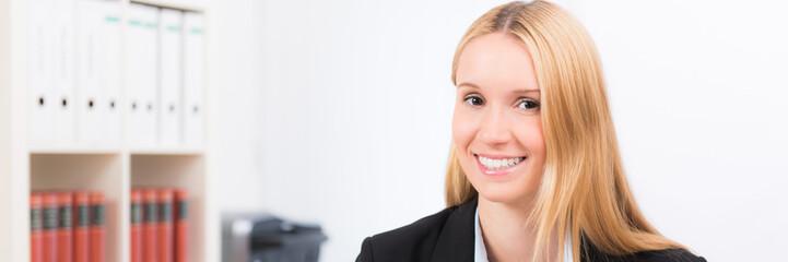 lächelnde blonde frau im büro