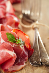 Cured Meat and vintage forks on textured  wooden background