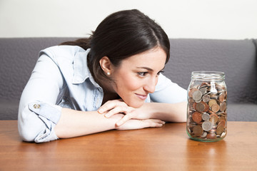Young woman looking at jar full of coins