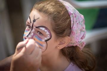 Spain, Valencia, Girl (6-7) while painting face