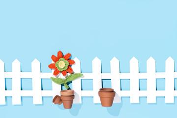 gehäkelte Blume im Topf an einem Zaun, blauer Hintergrund
