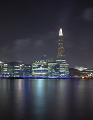 United Kingdom, London, Shard skyscraper illuminated at night and Thames river in foreground