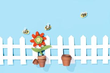 gehäkelte Blume im Topf mit Zaun und Bienen, blauer Hintergrund