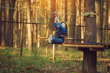 adorable cheerful little boy ziplining in the forest