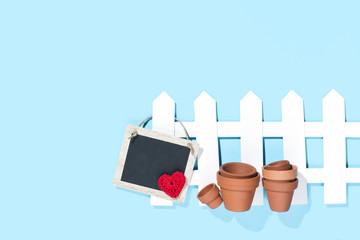 Zaun mit Schild, Herz und Töpfen, blauer Hintergrund