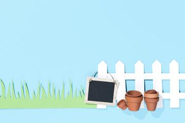 Zaun mit Schild, Töpfen und Rasen, blauer Hintergrund