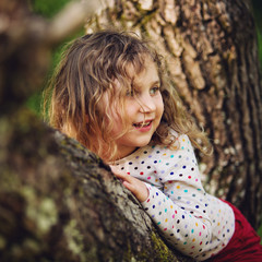Young girl sitting (4-5) in tree