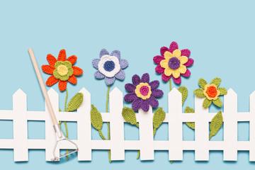 gehäkelte Blumen am Gartenzaun mit Harke