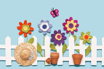 gehäkelte Blumen mit Zaun, Hut, Töpfen und einem Schmetterling